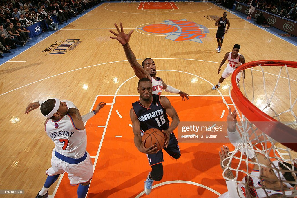 Kemba Walker #15 of the Charlotte Bobcats goes to the basket against Carmelo Anthony #7 and J.R. Smith #8 of the New York Knicks on March 29, 2013 at Madison Square Garden in New York City.