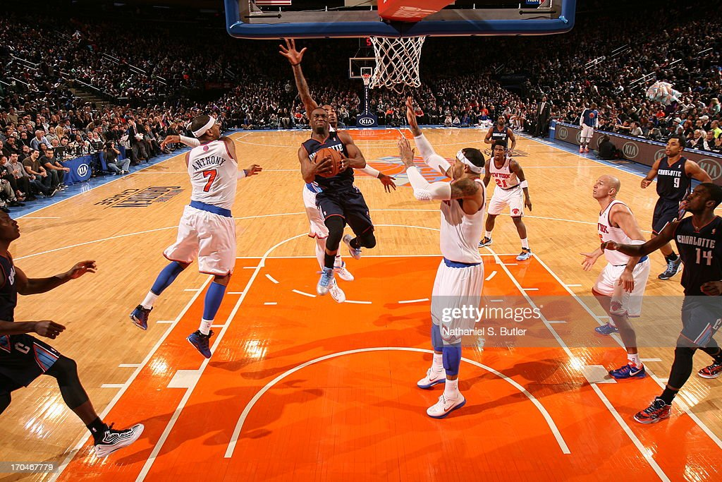 Kemba Walker #15 of the Charlotte Bobcats goes to the basket against Carmelo Anthony #7 and J.R. Smith #8 and Kenyon Martin #3 of the New York Knicks on March 29, 2013 at Madison Square Garden in New York City.