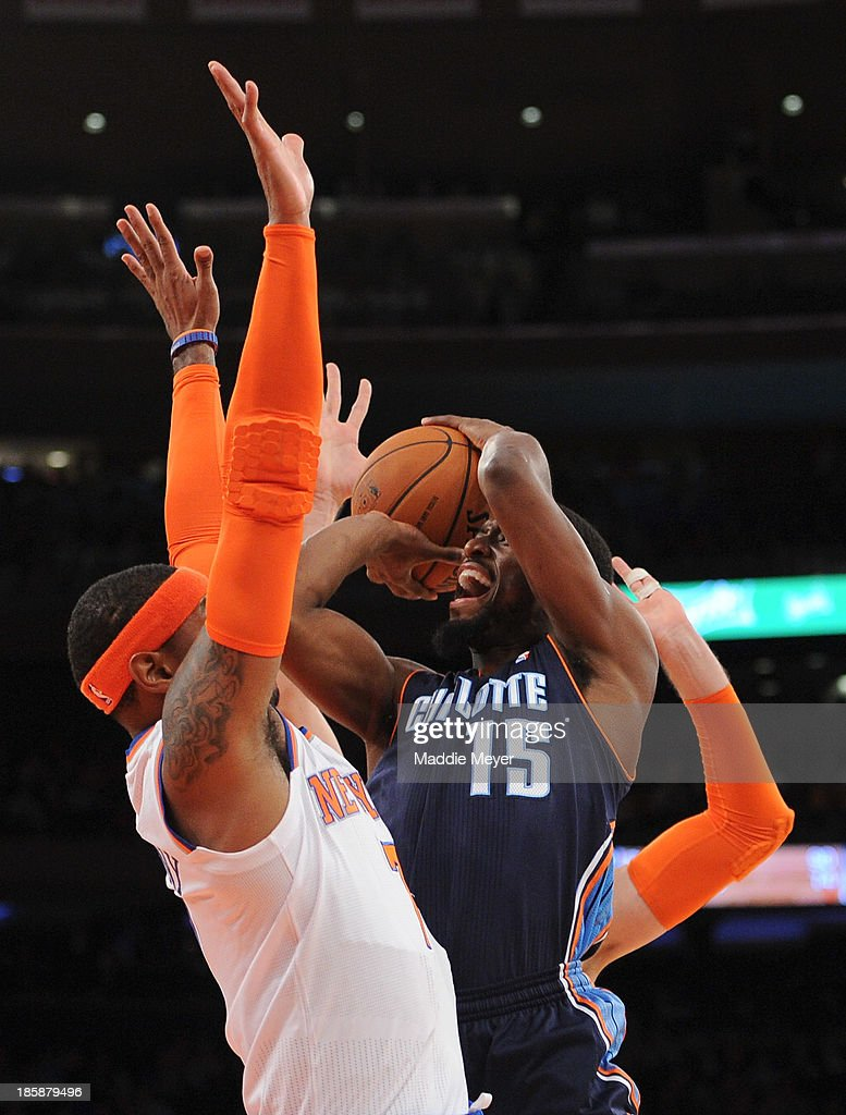 Kemba Walker #15 of the Charlotte Bobcats looks to shoot over Carmelo Anthony #7 of the New York Knicks during the first half of preseason play at Madison Square Garden on October 25, 2013 in New York City.