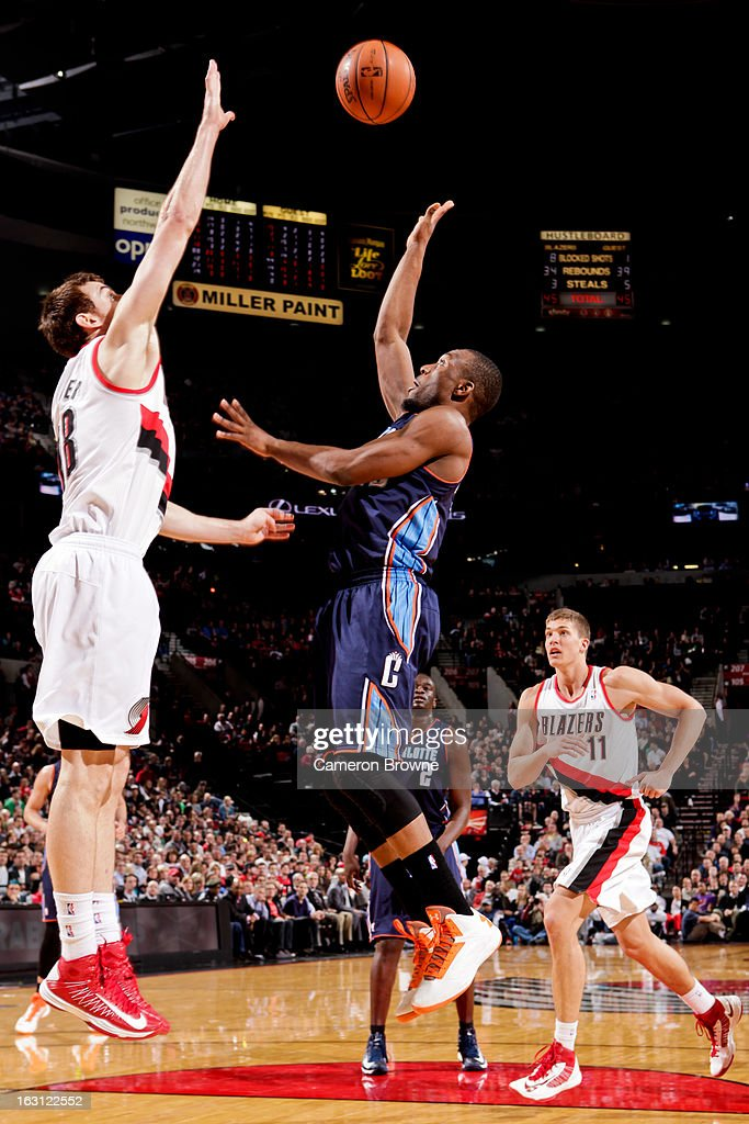 Kemba Walker #15 of the Charlotte Bobcats shoots in the lane against Victor Claver #18 of the Portland Trail Blazers on March 4, 2013 at the Rose Garden Arena in Portland, Oregon.