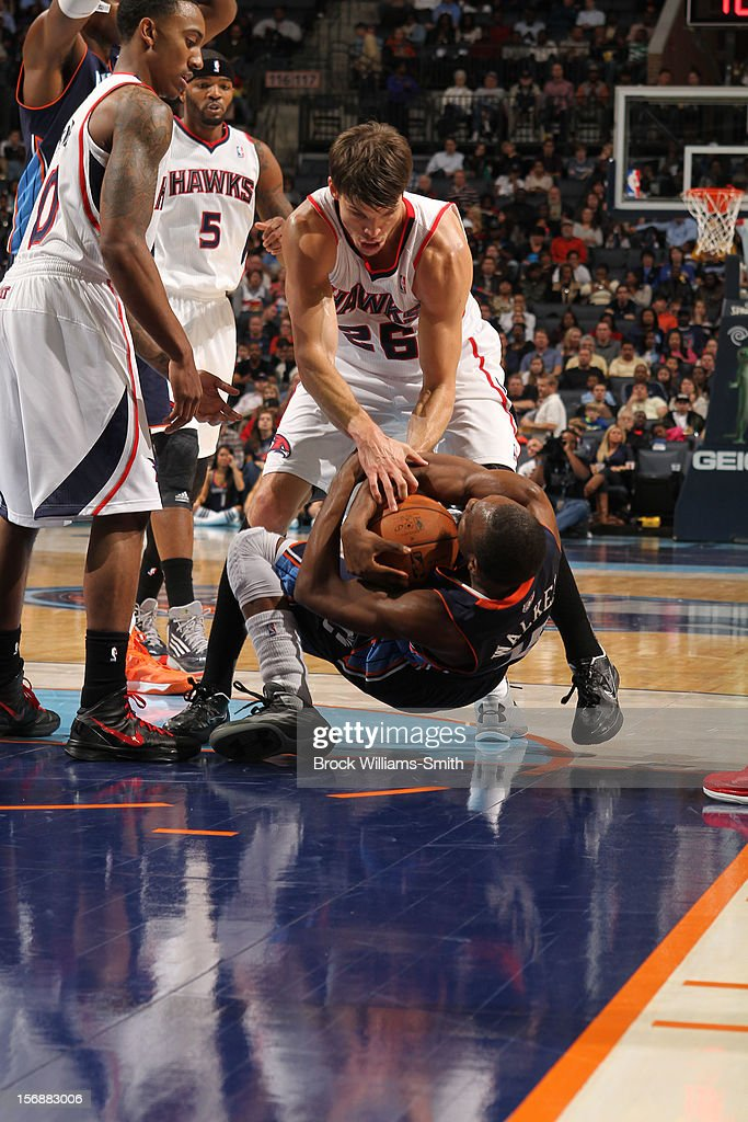 Kemba Walker #15 of the Charlotte Bobcats wrestles for the ball against Kyle Korver #26 of the Atlanta Hawks at the Time Warner Cable Arena on November 23, 2012 in Charlotte, North Carolina.