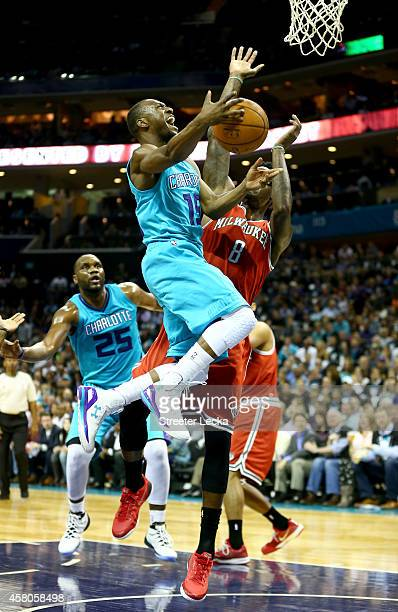 Kemba Walker of the Charlotte Hornets drives to the basket against Larry Sanders of the Milwaukee Bucks during their game at Time Warner Cable Arena...