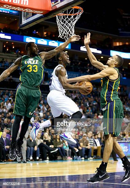 Kemba Walker of the Charlotte Hornets drives to the basket between teammates Trevor Booker and Rudy Gobert of the Utah Jazz during their game at Time...