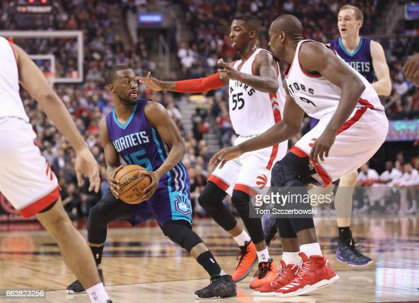 Kemba Walker of the Charlotte Hornets holds the ball as Delon Wright of the Toronto Raptors and Serge Ibaka guard him during NBA game action at Air...