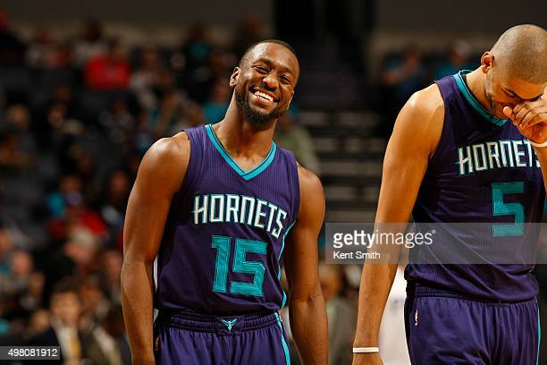 Kemba Walker of the Charlotte Hornets shares a laugh with teammate Nicholas Batum during the game against the Philadelphia 76ers at the Time Warner...