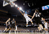 Kemba Walker of the Connecticut Huskies goes to the basket against Matt Howard and Shelvin Mack of the Butler Bulldogs during the National...