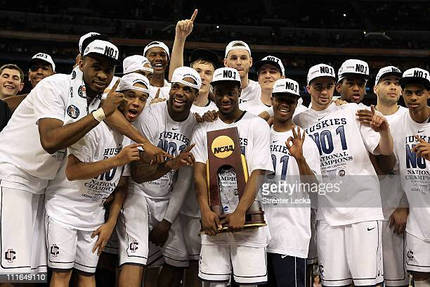 Kemba Walker of the Connecticut Huskies holds the trophy as he and his team celebrate after defeating the Butler Bulldogs to win the National...