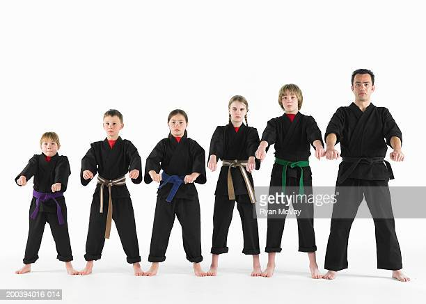 Kempo karate instructor holding karate pose with students