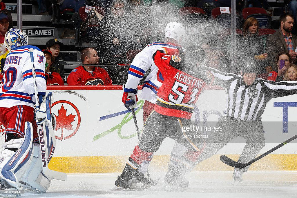Ken Agostino #51 of the Calgary Flames skates against Dan Girardi #5 and <a gi-track='captionPersonalityLinkClicked' href=/galleries/search?phrase=Henrik+Lundqvist&family=editorial&specificpeople=217958 ng-click='$event.stopPropagation()'>Henrik Lundqvist</a> #30 of the New York Rangers at Scotiabank Saddledome on March 28, 2014 in Calgary, Alberta, Canada.