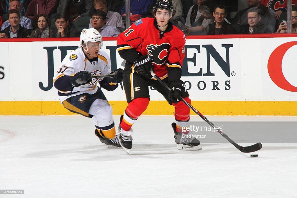 Ken Agostino #51 of the Calgary Flames skates the puck against <a gi-track='captionPersonalityLinkClicked' href=/galleries/search?phrase=Gabriel+Bourque&family=editorial&specificpeople=5627917 ng-click='$event.stopPropagation()'>Gabriel Bourque</a> #57 of the Nashville Predators at Scotiabank Saddledome on March 21, 2014 in Calgary, Alberta, Canada.