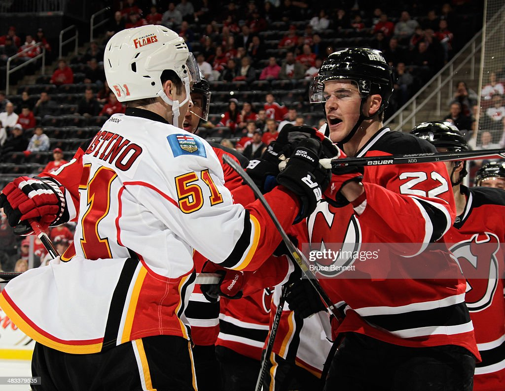 Ken Agostino #51 of the Calgary Flames tangles with Eric Gelinas #22 of the New Jersey Devils at the Prudential Center on April 7, 2014 in Newark, New Jersey. The Flames shutout the Devils 1-0.