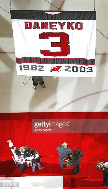 Ken Daneyko wearing his jersey waves to the crowd as his banner is lifted to the rafters during a pre game ceremony prior to the New Jersey Devils...
