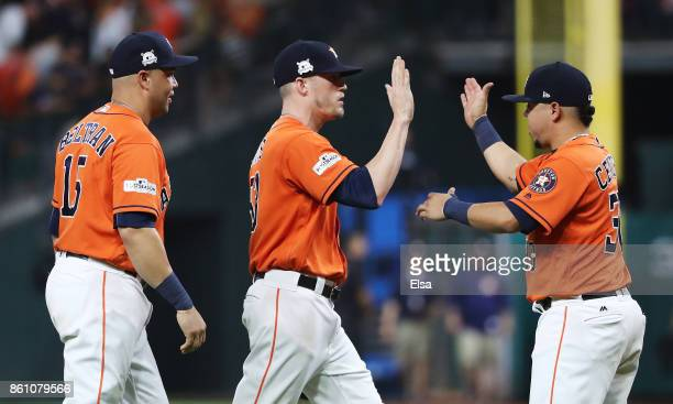 Ken Giles of the Houston Astros celebrates with teammates Carlos Beltran and Juan Centeno after their 2 to 1 win over the New York Yankees during...