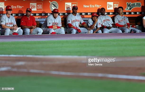 Ken Griffey Jr #3 of the Cincinnati Reds sits with teammates in the dugout during a game against the Florida Marlins in the first inning on June 6...