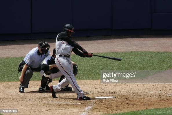Ken Griffey Jr of the Cincinnati Reds bats as the Mets' Mike Piazza catches and umpire Jerry Crawford looks on during the game against the New York...