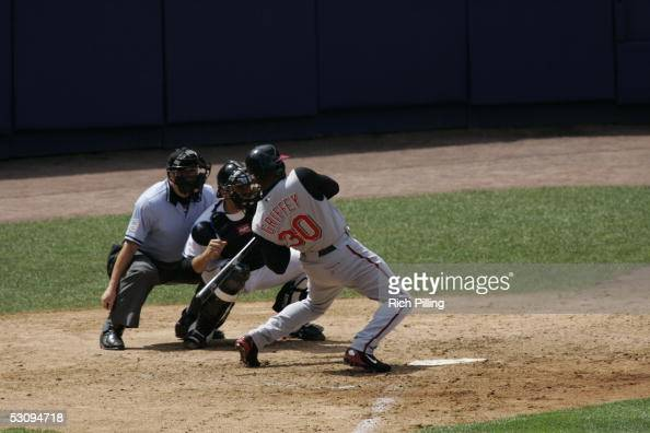 Ken Griffey Jr of the Cincinnati Reds leans away from on inside pitch as the Mets' Mike Piazza catches and umpire Jerry Crawford looks on during the...