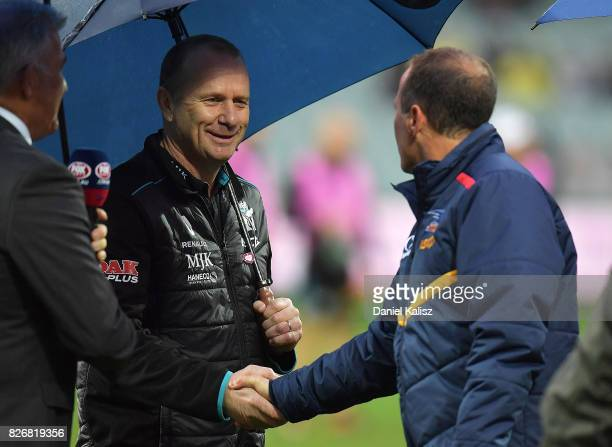 Ken Hinkley the coach of the Power shakes hands with Adelaide Crows Senior Coach Don Pyke prior to the round 20 AFL match between the Adelaide Crows...