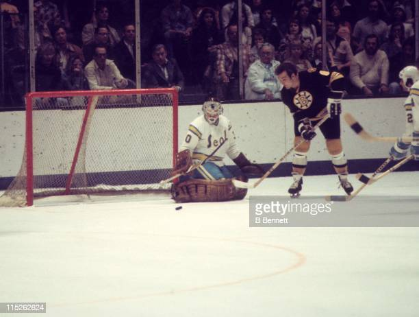 Ken Hodge of the Boston Bruins tries to score as goalie Gary Simmons of the California Golden Seals made the save during their game circa 1975 at the...