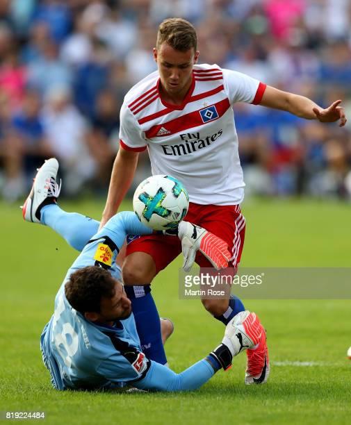 Ken Kronholm goalkeeper of Kiel tackles Luca Waldschmidt of Hamburg during the preseason friendly match between Holstein Kiel and Hamburger SV at...