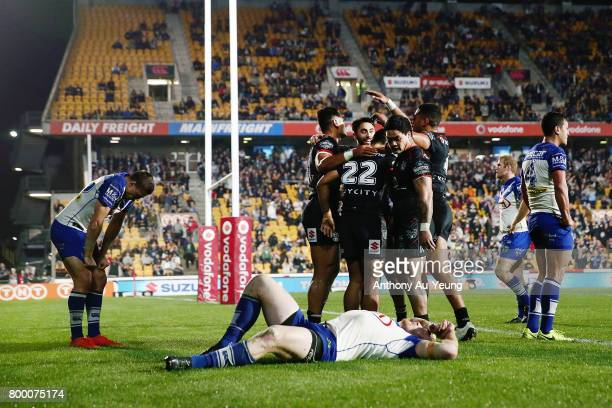 Ken Maumalo of the Warriors celebrates with teammates after scoring a try as James Graham of the Bulldogs takes a breather on the ground during the...