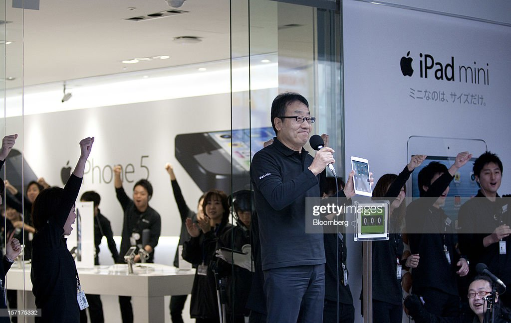 Ken Miyauchi, vice president and chief operating officer of Softbank Corp., center, holds an Apple Inc. iPad Mini during a ceremony as the device goes on sale at the Softbank store in the Ginza district of Tokyo, Japan, on Friday, Nov. 30, 2012. Softbank, the Japanese mobile-phone carrier that agreed this month to buy a $20 billion stake in Sprint Nextel Corp., started to sell the iPad Mini today. Photographer: Tomohiro Ohsumi/Bloomberg via Getty Images