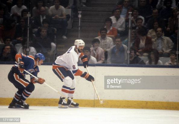 Ken Morrow of the New York Islanders passes the puck as Wayne Gretzky of the Edmonton Oilers follows behind during the 1984 Stanley Cup Finals in May...