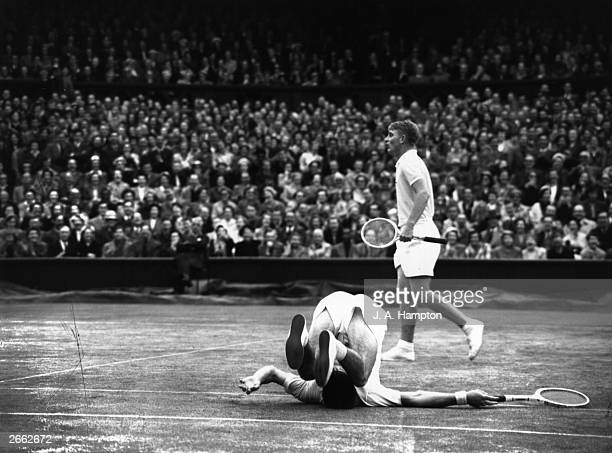 Ken Rosewall falls over backwards as fellow Australian Lew Hoad misses a shot in their doubles match against Vic Seixas and Tony Trabert at Wimbledon
