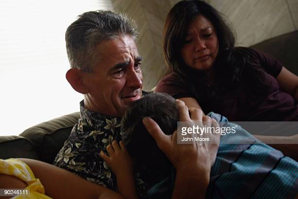 Ken Sheel terminally ill with pancreatic cancer embraces his son Malakai during a home hospice visit on August 31 2009 in Denver Colorado The...