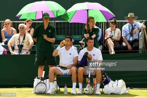 Ken Skupski of Great Britain and Neal Skupski of Great Britain take a break during the Gentlemen's Doubles second round match against Rohan Bopanna...
