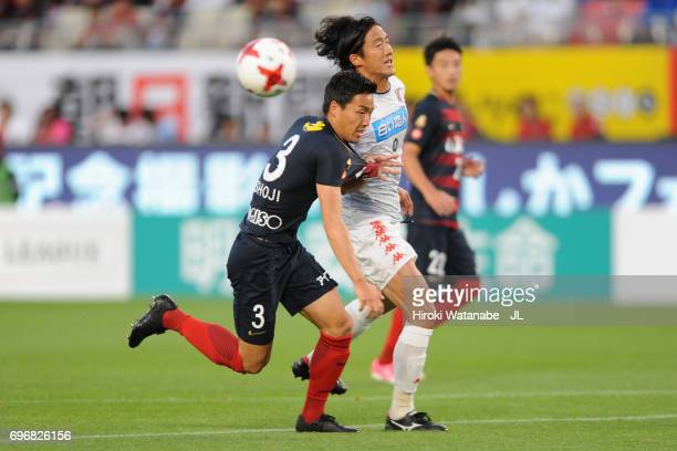 Ken Tokura of Consadole Sapporo and Gen Shoji of Kashima Antlers compete for the ball during the JLeague J1 match between Kashima Antlers and...