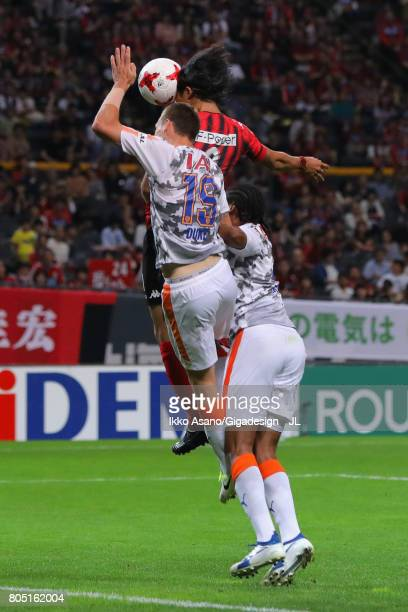 Ken Tokura of Consadole Sapporo competes for the ball against Mitchell Duke and Kanu of Shimizu SPulse during the JLeague J1 match between Consadole...