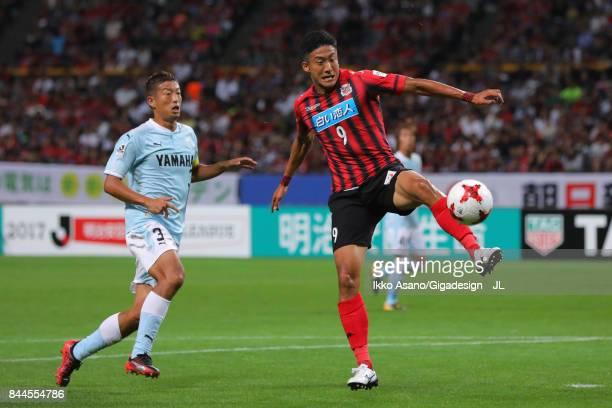 Ken Tokura of Consadole Sapporo controls the ball under pressure of Kentaro Oi of Jubilo Iwata during the JLeague J1 match between Consadole Sapporo...