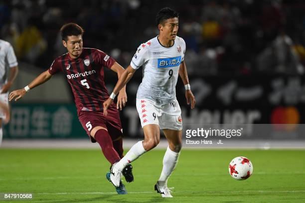 Ken Tokura of Consadole Sapporo controls the ball under pressure of Takuya Iwanami of Vissel Kobe during the JLeague J1 match between Vissel Kobe and...