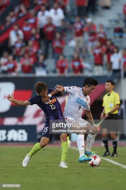 Ken Tokura of Consadole Sapporo controls the ball under pressure of Sho Inagaki of Sanfrecce Hiroshima during the JLeague J1 match between Sanfrecce...