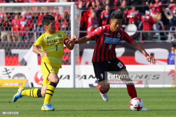 Ken Tokura of Consadole Sapporo controls the vall under pressure Hidekazu Otani of Kashiwa Reysol during the JLeague J1 match between Consadole...
