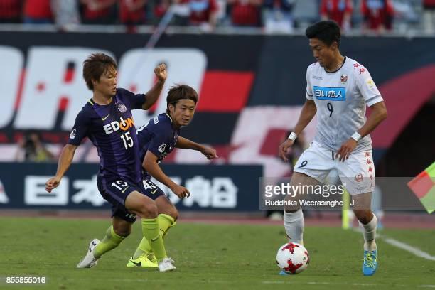 Ken Tokura of Consadole Sapporo takes on Sho Inagaki and Kenta Mukuhara of Sanfrecce Hiroshima during the JLeague J1 match between Sanfrecce...