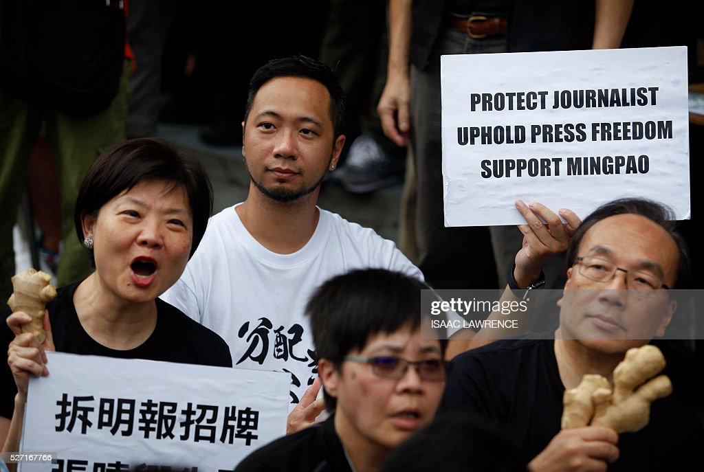 Ken Tsang (2nd L) holds a sign with people gathered outside the offices of Ming Pao during a rally organised by Journalist groups to protest the sacking of Ming Pao's Executive Chief Editor Keung Kwok-yuen in Hong Kong on May 2, 2016. / AFP / ISAAC