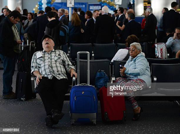 Ken Zemlak left naps as Esmelda Reed checks her phone while they both wait to board a flight to Panama City at Denver International Airport December...