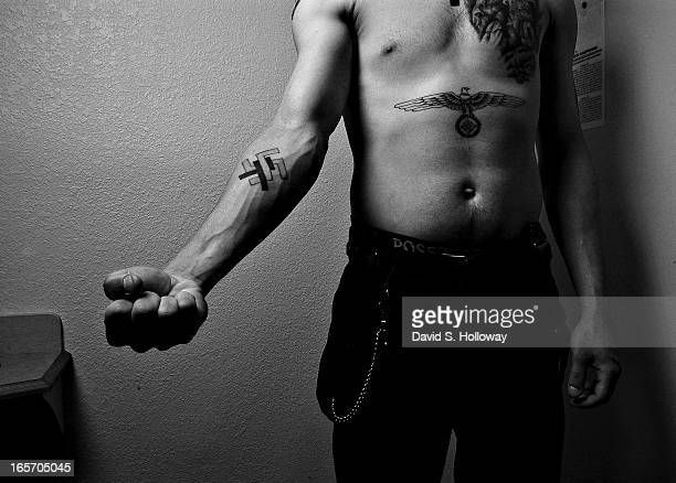 Ken Zrallack leader of the skinhead gang The Connecticut White Wolves shows off his tattoos in a motel room on May 8 2005 near Salem New Hampshire...