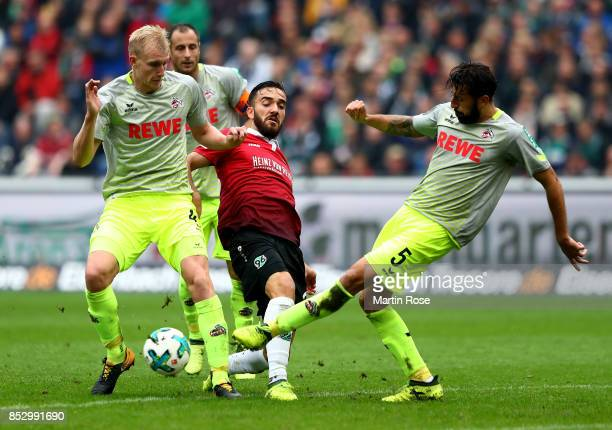 Kenan Karaman of Hannover and Frederik Soerensen and Dominic Maroh of Koeln battle for the ball during the Bundesliga match between Hannover 96 and 1...