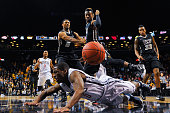 Kendall Anthony of the Richmond Spiders falls under JeQuan Lewis and Doug Brooks of the Virginia Commonwealth Rams during a quarterfinal game in the...