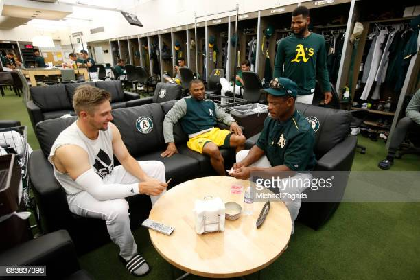 Kendall Graveman and Rickey Henderson of the Oakland Athletics play cards in clubhouse as Rajai Davis and Raul Alcantara watch on prior to the game...
