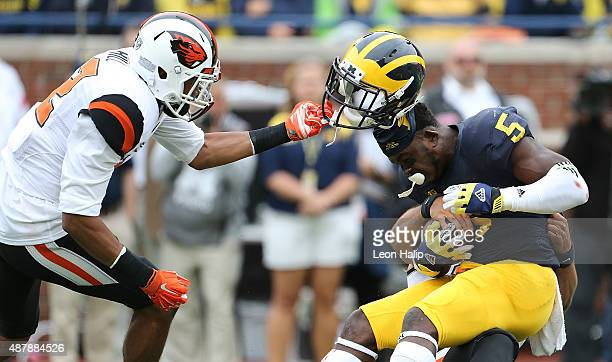 Kendall Hill of the Oregon State Beavers grabs the face mask of Jabrill Peppers of the Michigan Wolverines during the second quarter of the game on...