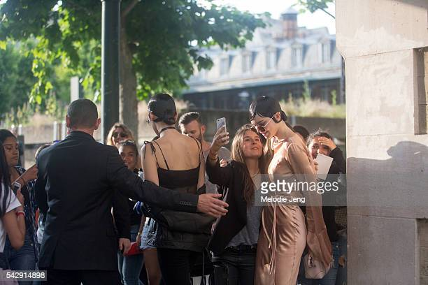 Kendall Jenner and Bella Hadid take selfies with students after the Givenchy show during Paris Fashion Week Men's SS17 on June 24 2016 in Paris France