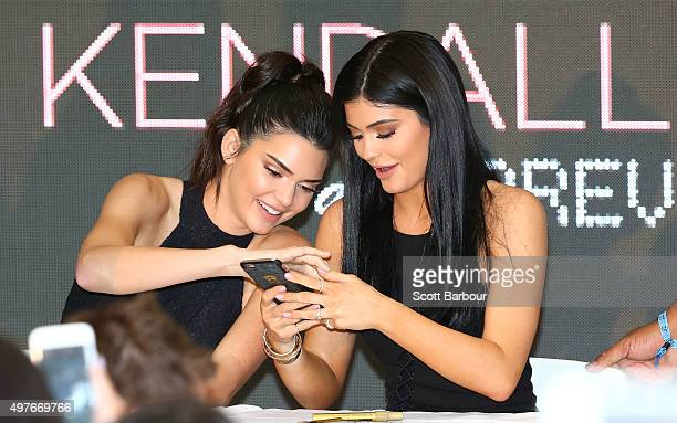 Kendall Jenner and Kylie Jenner look at their mobile phones as they arrive at Chadstone Shopping Centre on November 18 2015 in Melbourne Australia