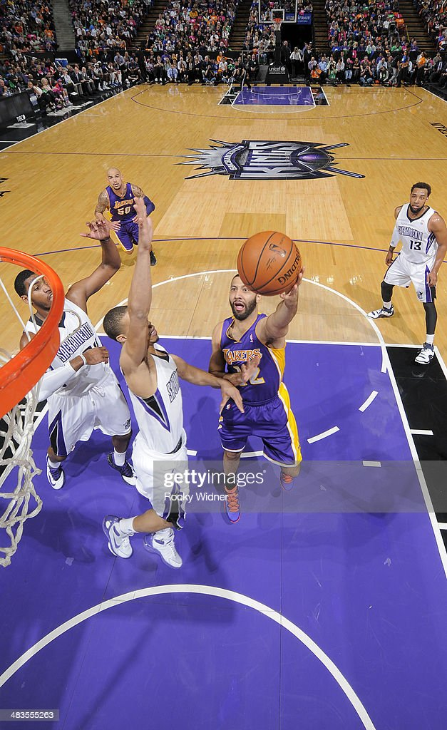 Kendall Marshall #12 of the Los Angeles Lakers shoots a layup against Jared Cunningham #9 of the Sacramento Kings on April 2, 2014 at Sleep Train Arena in Sacramento, California.