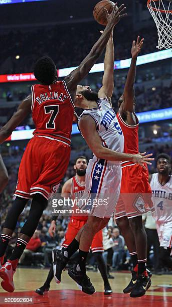 Kendall Marshall of the Philadelphia 76ers puts up a shot between Justin Holiday and Bobby Portis of the Chicago Bulls at the United Center on April...