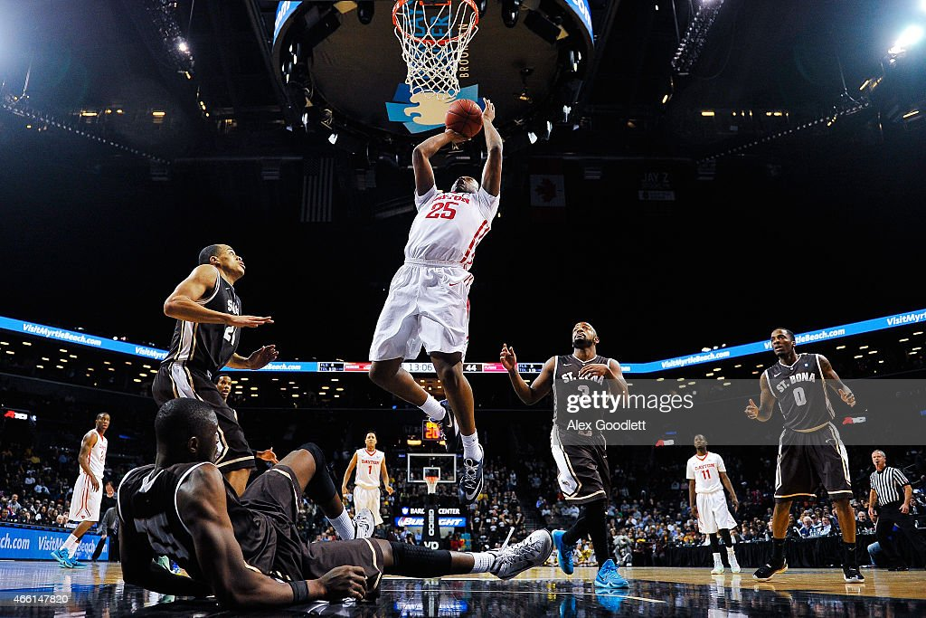 Kendall Pollard of the Dayton Flyers attempts a shot over Youssou Ndoye of the St Bonaventure Bonnies during a quarterfinal game in the 2015 Men's...