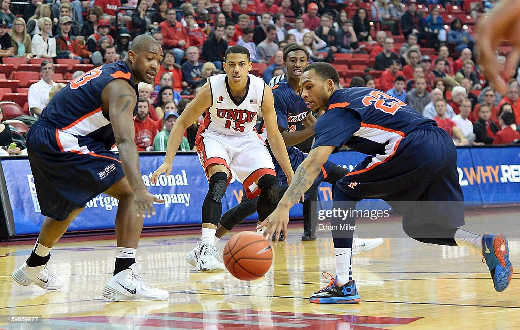Kendall Smith #15 of the UNLV Rebels passes the ball between James Johnson #33 and Alex Harris #23 of the California State Fullerton Titans during their game at the Thomas & Mack Center on December 28, 2013 in Las Vegas, Nevada. UNLV won 83-64.