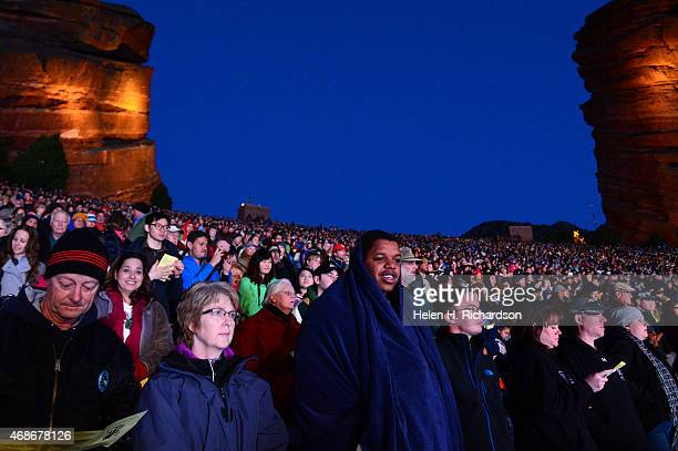 Kendall Thompkins middle and his friend Jordan Garton stay warm under blankets as they enjoy the 68th annual Easter sunrise service at Red Rocks...